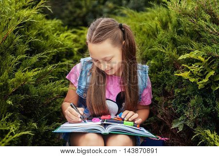 beautiful little girl writing in a notebook. Concept back to school