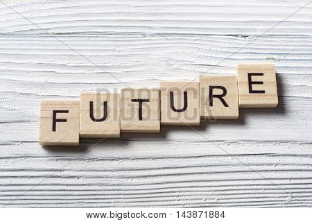 Future word written on wood abc cube with wooden background.