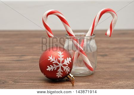 Two candy canes in a jar with a christmas bauble