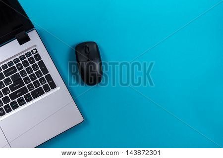 Office table desk with set of colorful supplies, white blank note pad, cup, pen, pc, crumpled paper, flower on blue background. Top view and copy space for text.