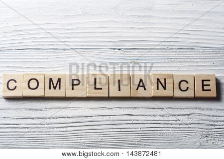 Compliance word written on wood abc block at wooden background
