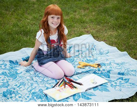 Little redhead girl sitting on the plaid with pencils and album for drawing