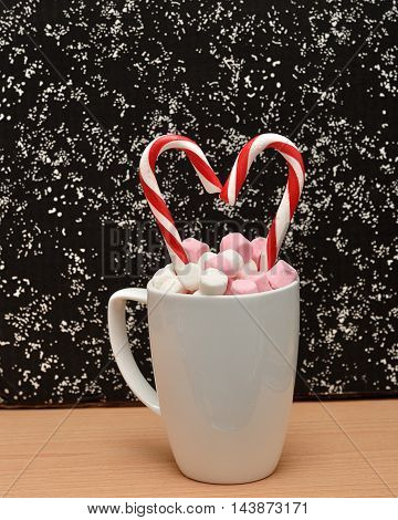 A mug filled with small marshmallows with two candy canes that is in a heart shape against a black and white background