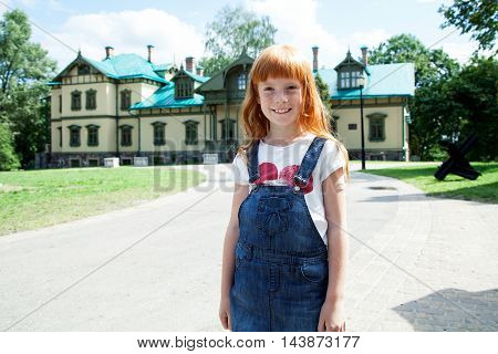 Cute little girl standing against a green lawn and big village house and smiling