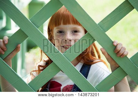 Close up portrait of a smiling ginger girl with freckles standing behind green wooden fencing