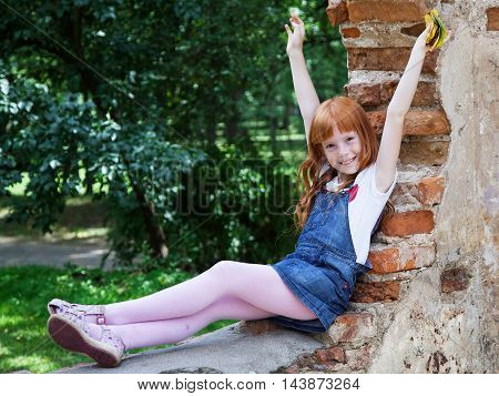 Little ginger girl sitting on the red brick wall in the park