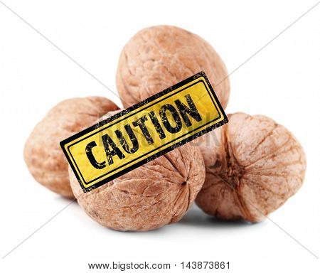 Allergy danger concept. Heap of walnuts with stamp caution on white background.