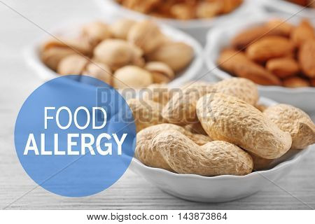 Allergy danger concept. Different kinds of nuts in bowls on white wooden background. Text food allergy.