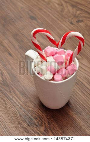 A mug filled with small marshmallows with two candy canes that is in a heart shape