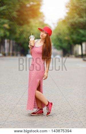 Fashion city portrait of stylish hipster woman with milk shake, red striped dress, red cap and sneakers, makeup, long brunette hairs, walking alone at weekend, enjoy vacation in Europe, modern trendy summer outfit. Evening soft sunlight.