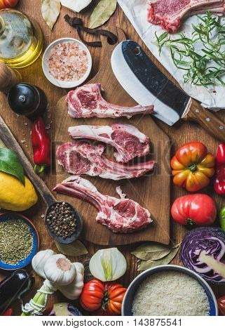 Ingredients for cooking dinner. Raw uncooked lamb meat ribs, rice, oil, spices and vegetables over wooden background, top view, vertical composition