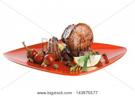 roast beef meat fillet medallion with cherry tomatoes and hot peppers on red plate isolated on white background