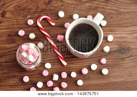 A mug filled with black coffee surrounded with small white and pink marshmallows and a candy cane