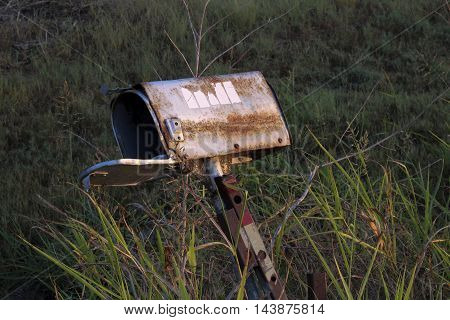 Derelict mailbox sits empty with door open.
