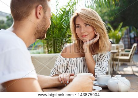 Young beautiful couple speaking, smiling, drinking tea, resting, sitting in cafe