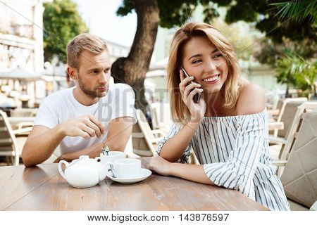 Young beautiful couple sitting in cafe. Girl speaking on phone while her boyfriend being bored.