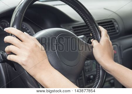The hands of a girl with a stylish manicure lies on the handlebars in a saloon car