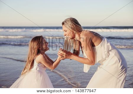 Beautiful mother and daugther laughing together on the beach