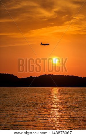 Silhouette Of Passenger Airplane Landing At Sunset