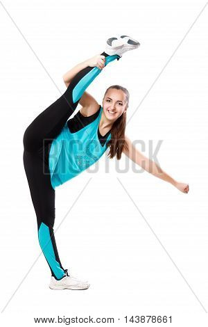 Young professional cheerleader stands in vertical splits. Isolated over white.