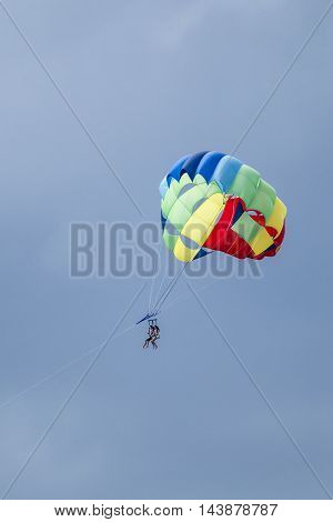 Two unidentified people take a parasail ride together in the sky.