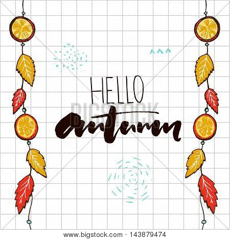 Hello autumn inscription on notebook squared paper. Hanging autumn garland decorations with orange slices and golden leaves
