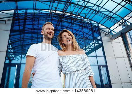 Young beautiful couple smiling, embracing, rejoicing, walking around city