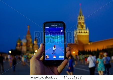 Moscow, Russia - July 31: Male hand holding a Samsung smartphone with a running modern augmented reality game Pokemon Go on the background of Red Square landmarks at night