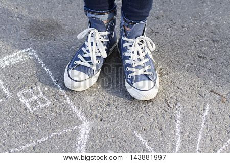 Feet girl in sneakers cost about drawing a chalk on the pavement