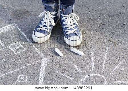 About drawing with chalk on the pavement feet in fashionable sneakers