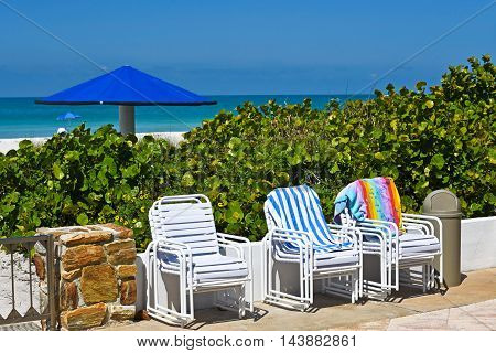 Outdoor Chairs stacked on patio with a view of the Ocean and White Sandy Beach of Anna Maria Island Florida in the background