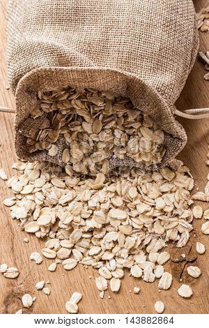 Dieting. Oat cereal in burlap sack on wooden surface. Healthy food for lowering cholesterol protect heart.