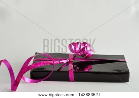 A black gift box decorated with a pink ribbon isolated on a white background