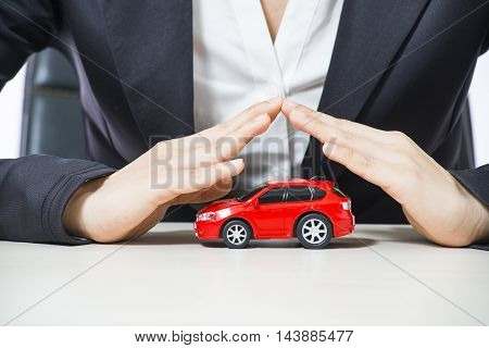 car covered of woman hands - insurance concept