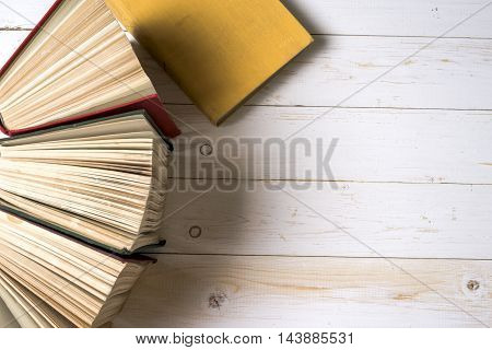 Top view of colorful hardback books in a circle. Open book fanned pages isolated on white background free copy space. Back to school copy space. Education background.