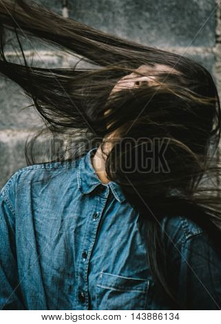 Blurred image (defocused) of asian woman flicking her black hair,vintage style