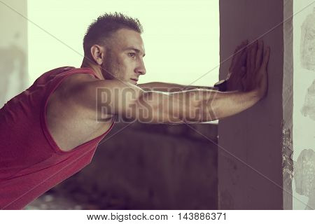 Muscular athletic built young man stretching out in a ruin building before workout