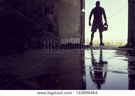 Muscular athletic built young athlete working out in a ruin building next to a puddle of water. Crossfit training with barbells and kettlebell deadlifting