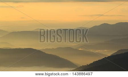Layer of mountains in the mist at sunrise time In view panorama.edit warm tone