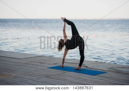 Image of a pretty woman doing yoga at the lake.