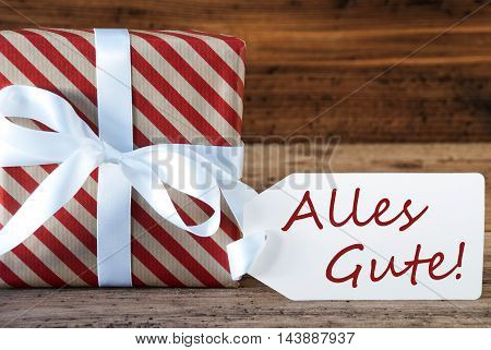 Macro Of Christmas Gift Or Present On Wooden Background. Card For Seasons Greetings, Best Wishes Or Congratulations. White Ribbon With Bow. German Text Alles Gute Means Best Wishes
