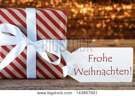 Macro Of Christmas Gift Or Present On Atmospheric Wooden Background. Card For Seasons Greetings Or Congratulations. White Ribbon With Bow. German Text Frohe Weihnachten Means Merry Christmas