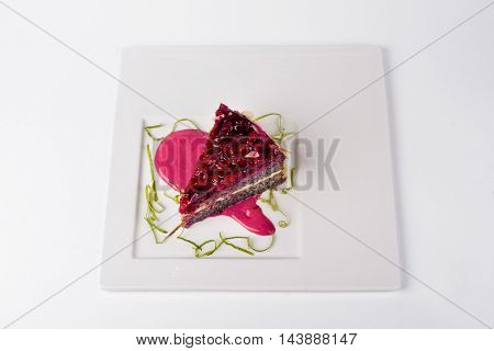 Poppy raspberry cake with jam on white plate background