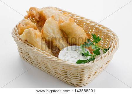 Cod in beer batter with tartar sauce in bamboo basket on white background