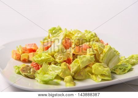 Pieces of fried chicken tomatoes Chinese lettuce and croutons with a spicy sauce