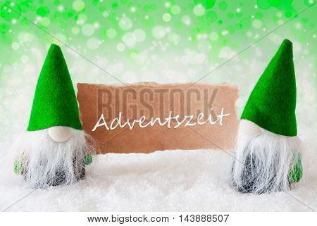 Christmas Greeting Card With Two Green Gnomes. Sparkling Bokeh And Natural Background With Snow. German Text Adventszeit Means Advent Season