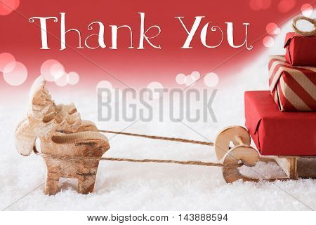 Moose Is Drawing A Sled With Red Gifts Or Presents In Snow. Christmas Card For Seasons Greetings. Red Christmassy Background With Bokeh Effect. English Text Thank You