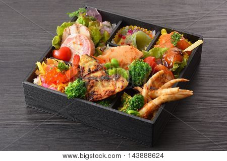 Bento meal of grilled fish salmon eggs bamboo shoots radish tomatoes pork and lettuce on wooden table