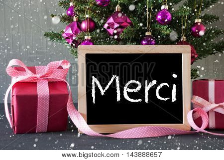 Chalkboard With French Text Merci Means Thank You. Christmas Tree With Rose Quartz Balls, Snowflakes. Gifts Or Presents In The Front Of Cement Background.