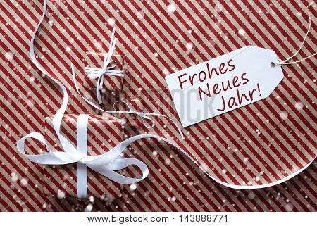 Two Gifts Or Presents With White Ribbon. Red And Brown Striped Wrapping Paper. Christmas Or Greeting Card With Snowflakes. Label With German Text Frohes Neues Jahr Means Happy New Year